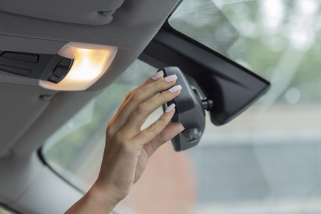 rear view mirror: the girl in the cabin of the car adjusts the rear view mirror Stock Photo