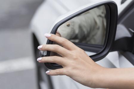 het meisje in de auto met mooie manicure past de achteruitkijkspiegel