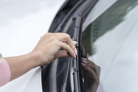 Girls hand corrects wipers on the glass of the car.