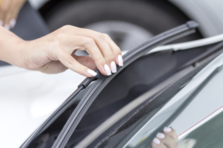 Girls hand regulates and inspects the wipers on the glass of the car.
