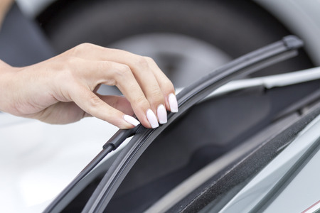 Girls hand corrects wipers on the glass of the car. Banco de Imagens - 61694657