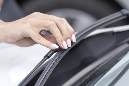 Girls hand regulates the wiper of the car. Banco de Imagens