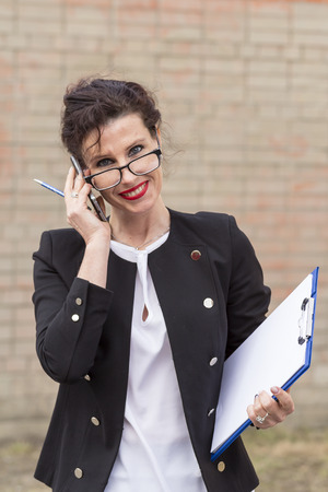 businesslike: smiling woman with a folder in his handand and speaks on a mobile telephone