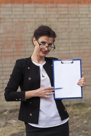 adulthood: business woman in glasses smiling with a folder in his hand