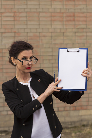 adulthood: woman in glasses and black suit holding a clip board
