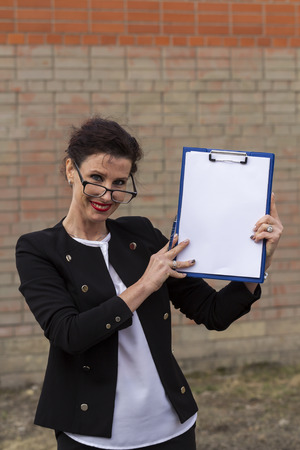 businesslike: business woman in glasses smiling with a folder in his hand