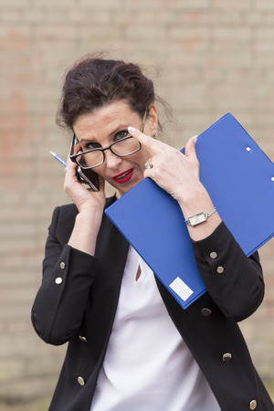 clip board: business woman in glasses and black suit holding a clip board
