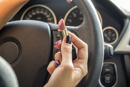 keeps: Arm girls with trendy manicure keeps lipstick while driving in the car.