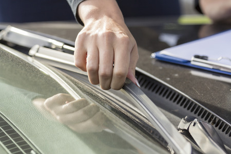 Girls hand regulates and inspects the wipers on the glass of the car