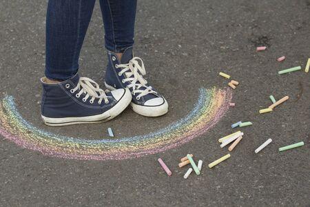 I piedi con le scarpe da ginnastica sono sul marciapiede accanto all'immagine dell'arcobaleno