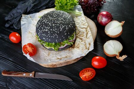 Black burger with tomatoes, with Chinese cabbage, onions on a black wooden background