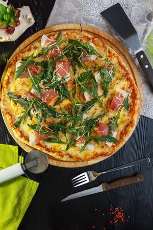 Pizza with bacon, cheese and herbs on a wooden dish on a black wooden background