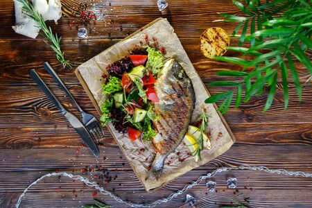 Grilled fish with vegetables and herbs on the kitchen board on a brown wooden background