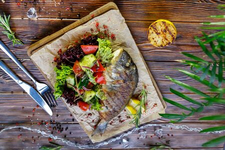 Grilled fish with vegetables and herbs on the kitchen board on a brown wooden background Stockfoto - 130053286