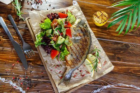 Grilled fish with vegetables and herbs on the kitchen board on a brown wooden background Stockfoto - 130053284