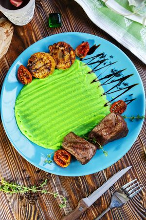Meat with a side dish of mashed potatoes on a plate on a wooden brown background Stockfoto