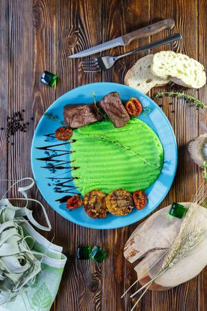Meat with a side dish of mashed potatoes, bread, a knife and a fork on a plate on a wooden brown background