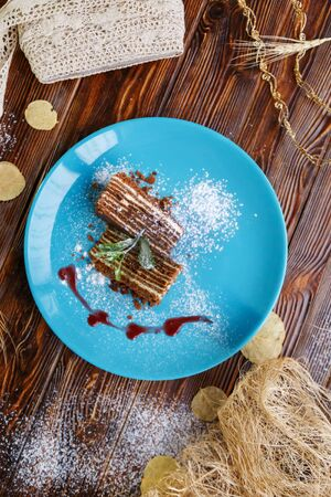Slices of cake on a blue plate on a brown wooden background Stockfoto