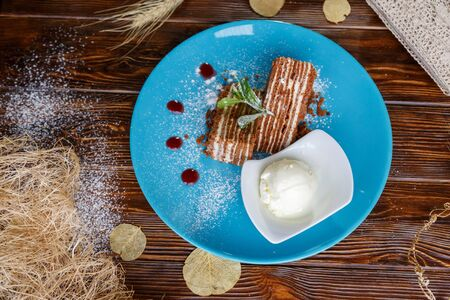 Ice cream ball and pieces of cake on a blue plate on a wooden background
