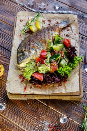 Grilled fish with vegetables and herbs on the kitchen board on a brown wooden background Stockfoto - 130058500