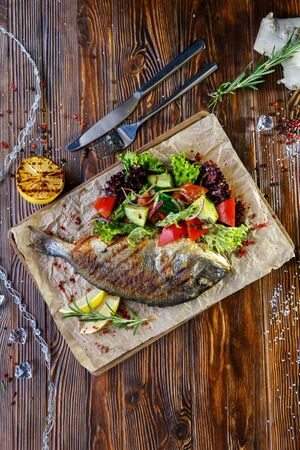 Grilled fish with vegetables and herbs on the kitchen board on a brown wooden background Stockfoto - 130058502