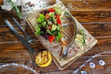 Grilled fish with vegetables and herbs on the kitchen board on a brown wooden background Stockfoto - 130058503