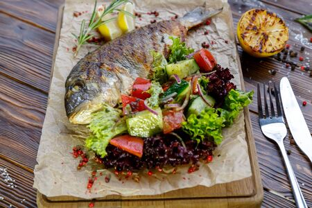 Grilled fish with vegetables and herbs on the kitchen board on a brown wooden background Stockfoto - 130058554