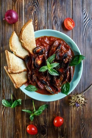 Mussels in tomato sauce with garlic in a blue plate on a brown wooden background