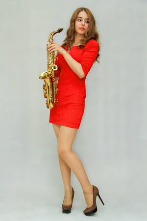 A beautiful girl in a red dress sits and holds in her hands a golden saxophone Banque d'images