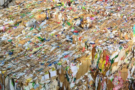Compressed paper and cardboard prepared for industrial ecological recycling
