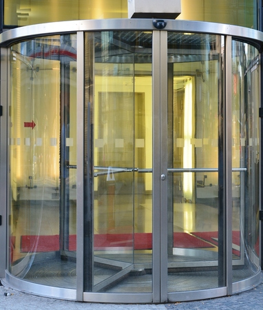 Modern revolving door as entrance to office building or hotel Standard-Bild