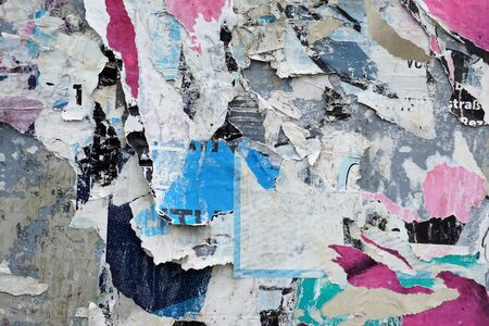 Colorful torn posters on grunge old walls as creative and abstract background