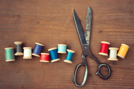 old spools: Old scissors and wooden spools of colored thread lie on a wooden table