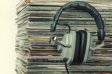 audiophile: Audiophile headphones and a stack of old vinyl records.Toned photo.