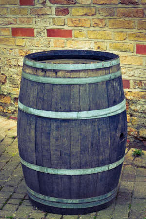 winy: Old big barrel for wine stands near a barn