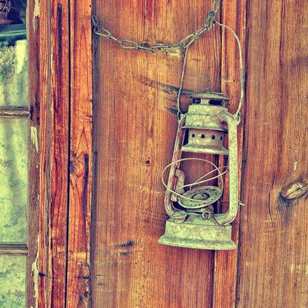 kerosene lamp: Old kerosene lamp on the wall of wooden house Stock Photo