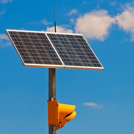 trafficlight: Sunny battery on a traffic-light on a background blue sky Stock Photo