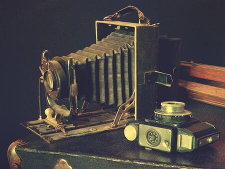 fascination: Old cameras, wooden tripod lie on a suitcase Stock Photo