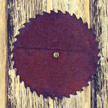 ferrous: An old ferrous saw hangs on a wooden wall