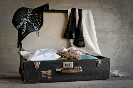 open suitcase: Open suitcase with old things on the brick wall background Stock Photo