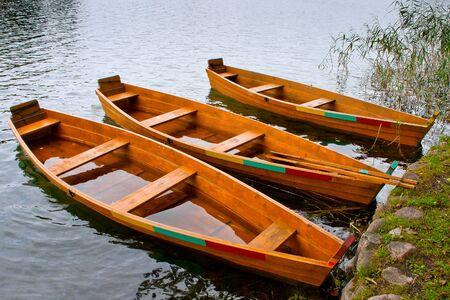 Drie houten roeiboot in de buurt van de kust Stockfoto