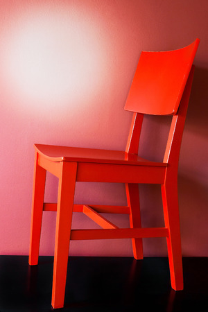 wooden chair: Red wooden chair on a black floor