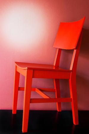 silla de madera: silla de madera roja en un suelo negro Foto de archivo
