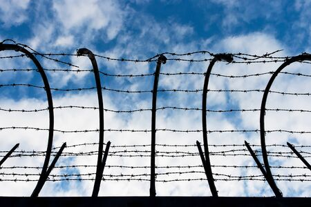 Barbed wire fence on the background of the cloudy sky