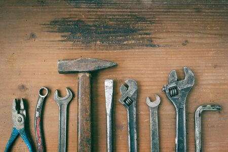 the outmoded: Hammer, pliers and wrenches old on a wooden board