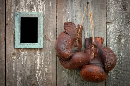 Old boxing gloves and photo frame on a wooden wall