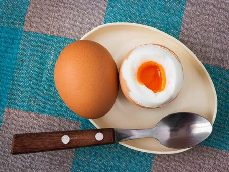 boiled eggs: Two boiled eggs and a spoon with wooden handle