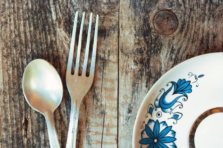 diningroom: The spoon, a fork and a plate standing on the wooden table Stock Photo