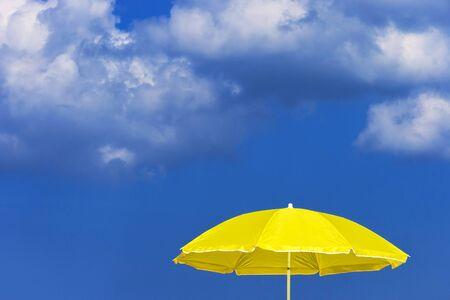warm climate: Yellow sun umbrella against the blue sky