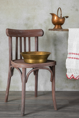 antique chair: Antique utensils for washing, old wooden chair and a white towel on the table Stock Photo